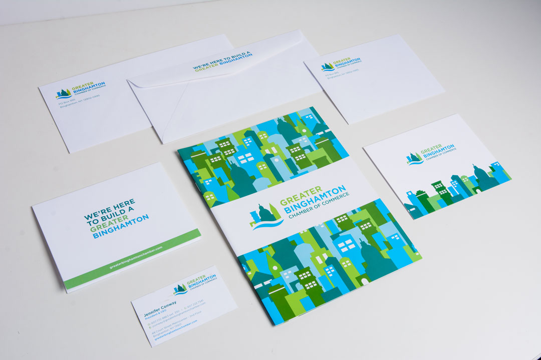 Greater Binghamton Chamber of Commerce stationery laid out on a white background. The set includes front and back of envelopes, invites, a brochure, and business cards all showing the new GBBC logo.