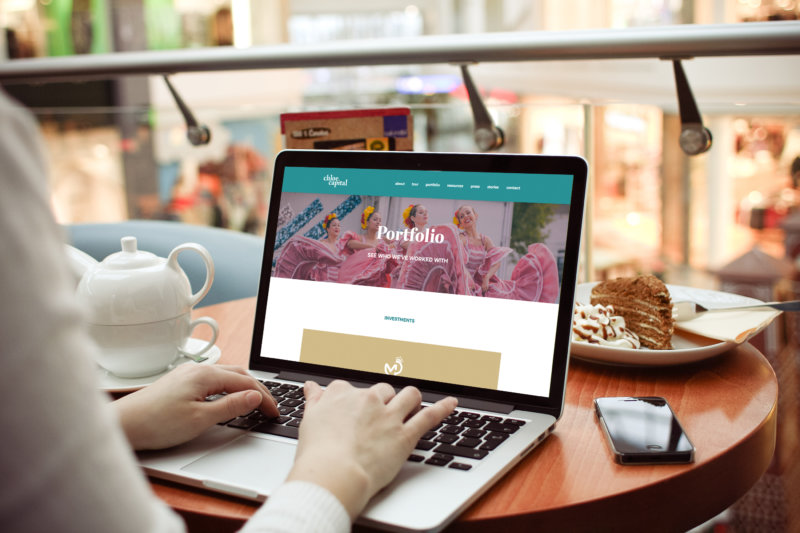 A woman's hand working on a macbook pro showing the Chloe Capital website on a small wood table in-front of a pastry on a plate.