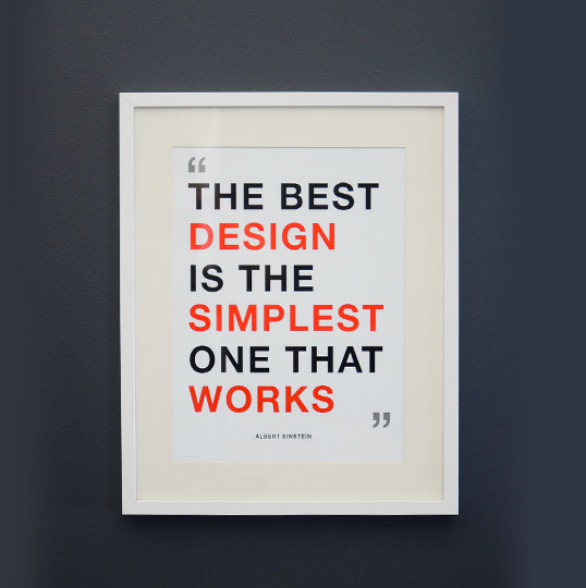 Albert Einstein quote The best design is the simplest one that works poster framed on a gray wall with black and red text