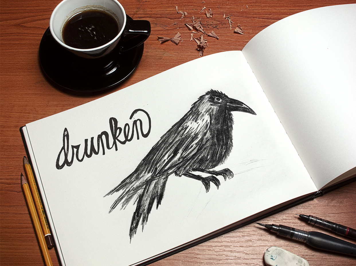 Pencil sketch of a crow drawn in an open notebook that was place on a table with coffee and pencil shavings